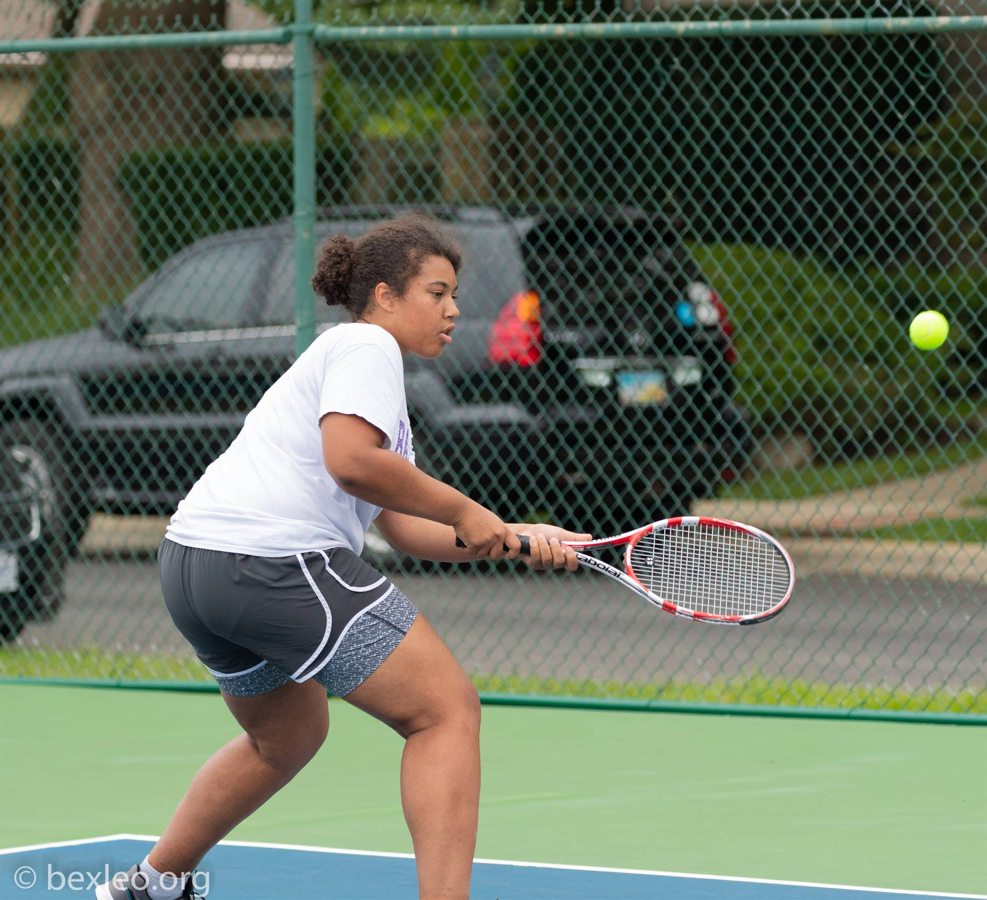 JV Tennis player hitting tennis ball