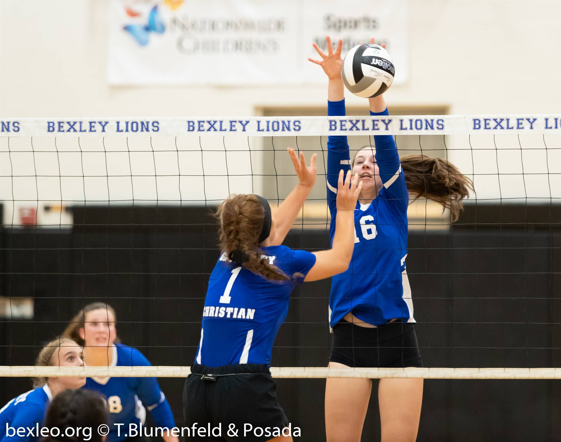 volleyball player blocking the ball at the net