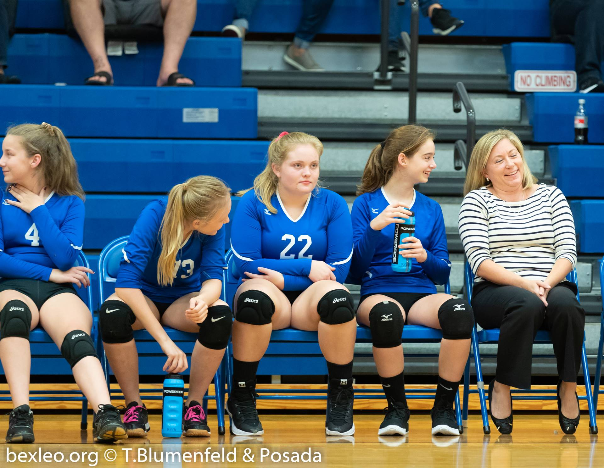 Volleyball players sharing a laugh with their coach