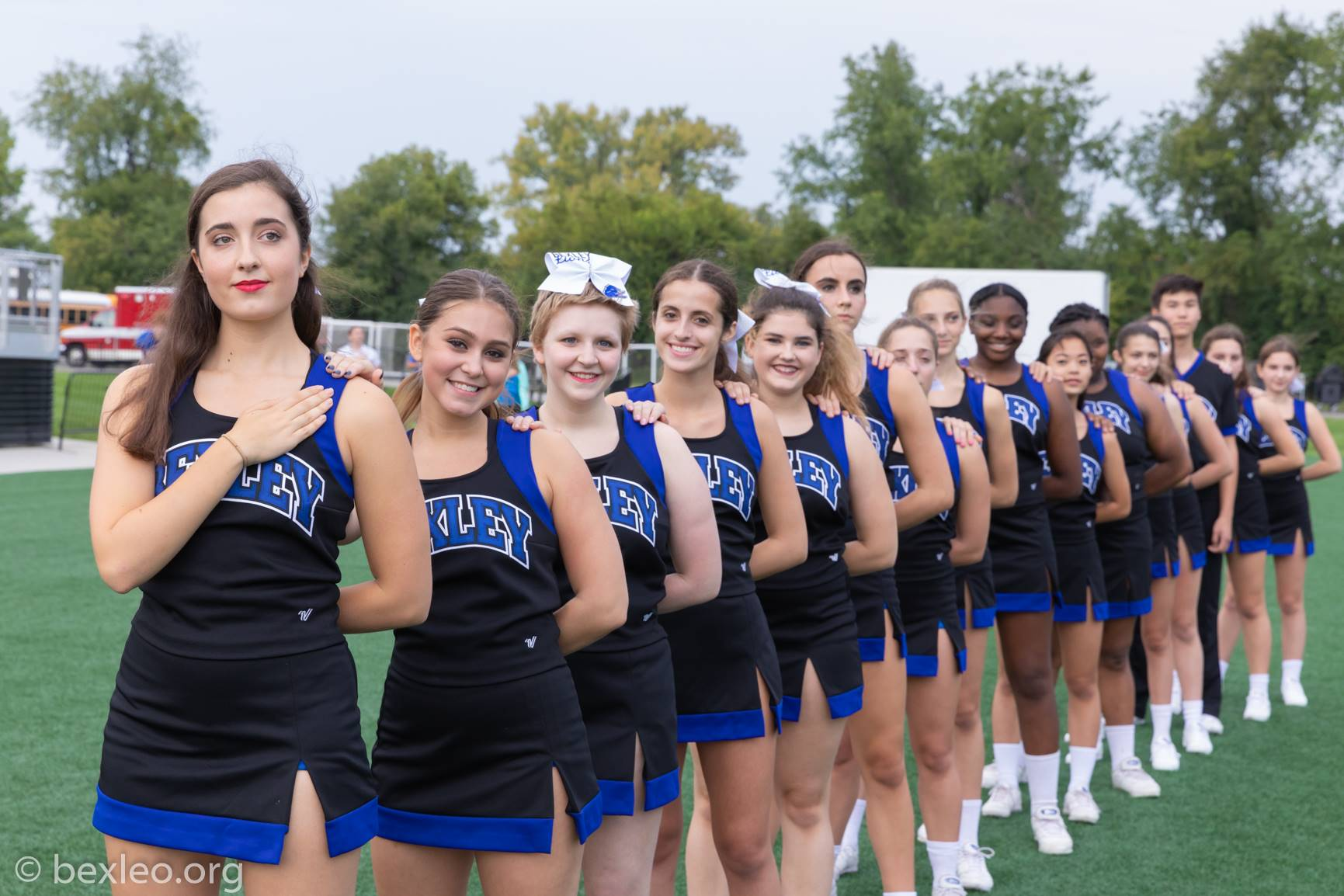 Cheerleaders stand for the anthem