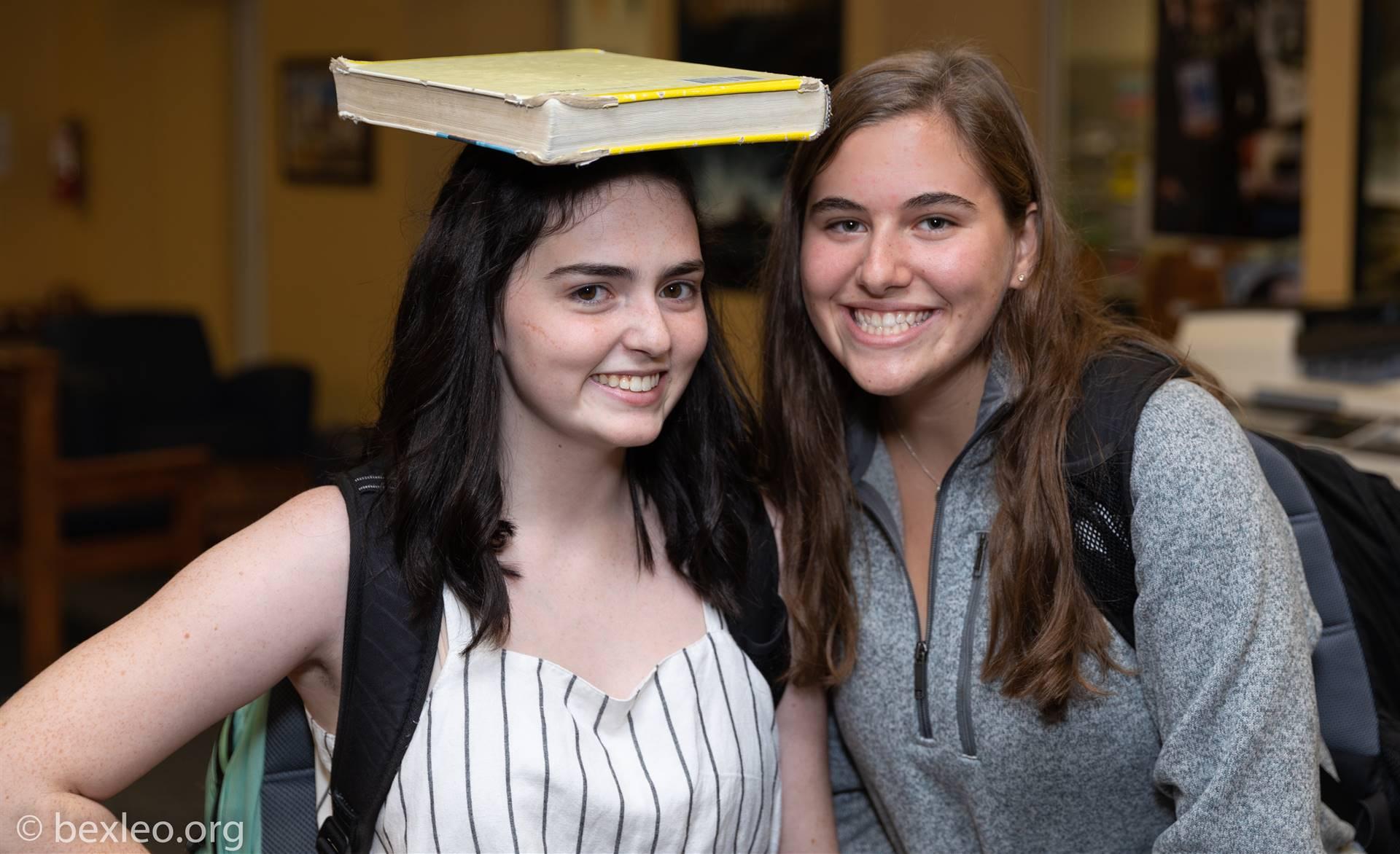 A math student balances her calculus textbook on her head next to a friend