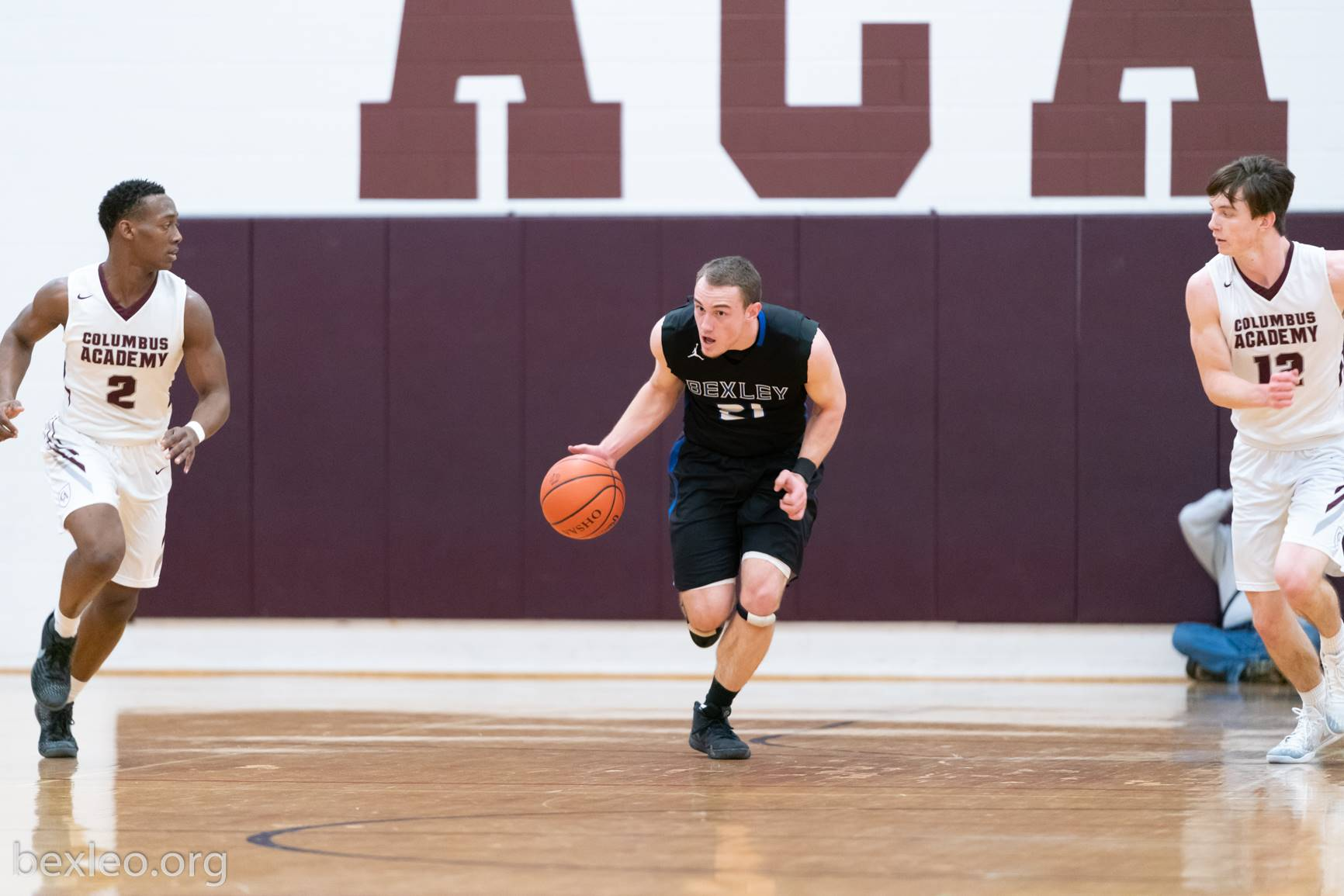 Boys Basketball players brings the ball upcourt vs Columbus Academy