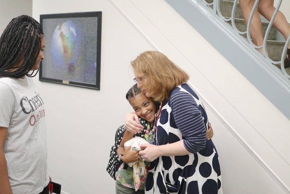 Ms. Hetzler hugs a student.